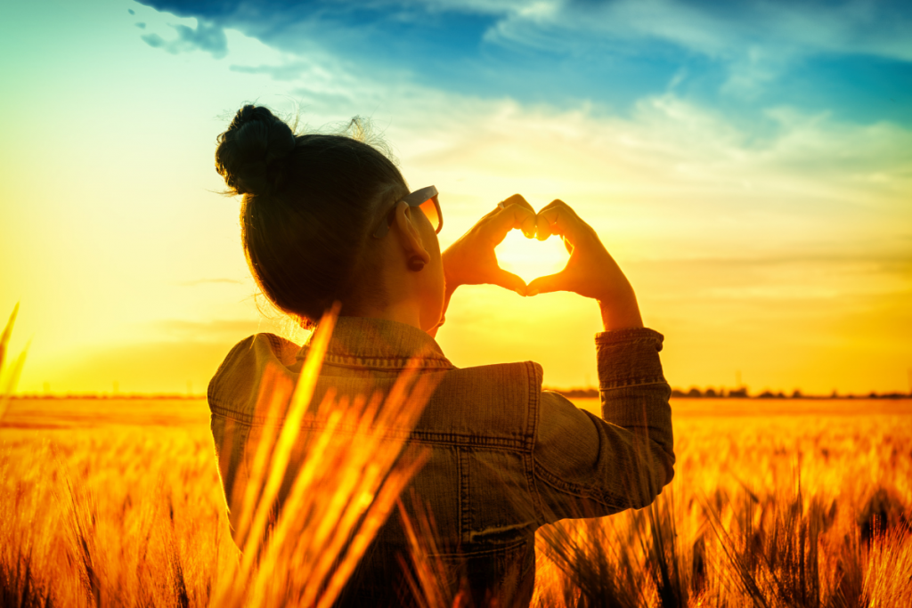 Women standing in field with a heart shape made with her hands at sunset.